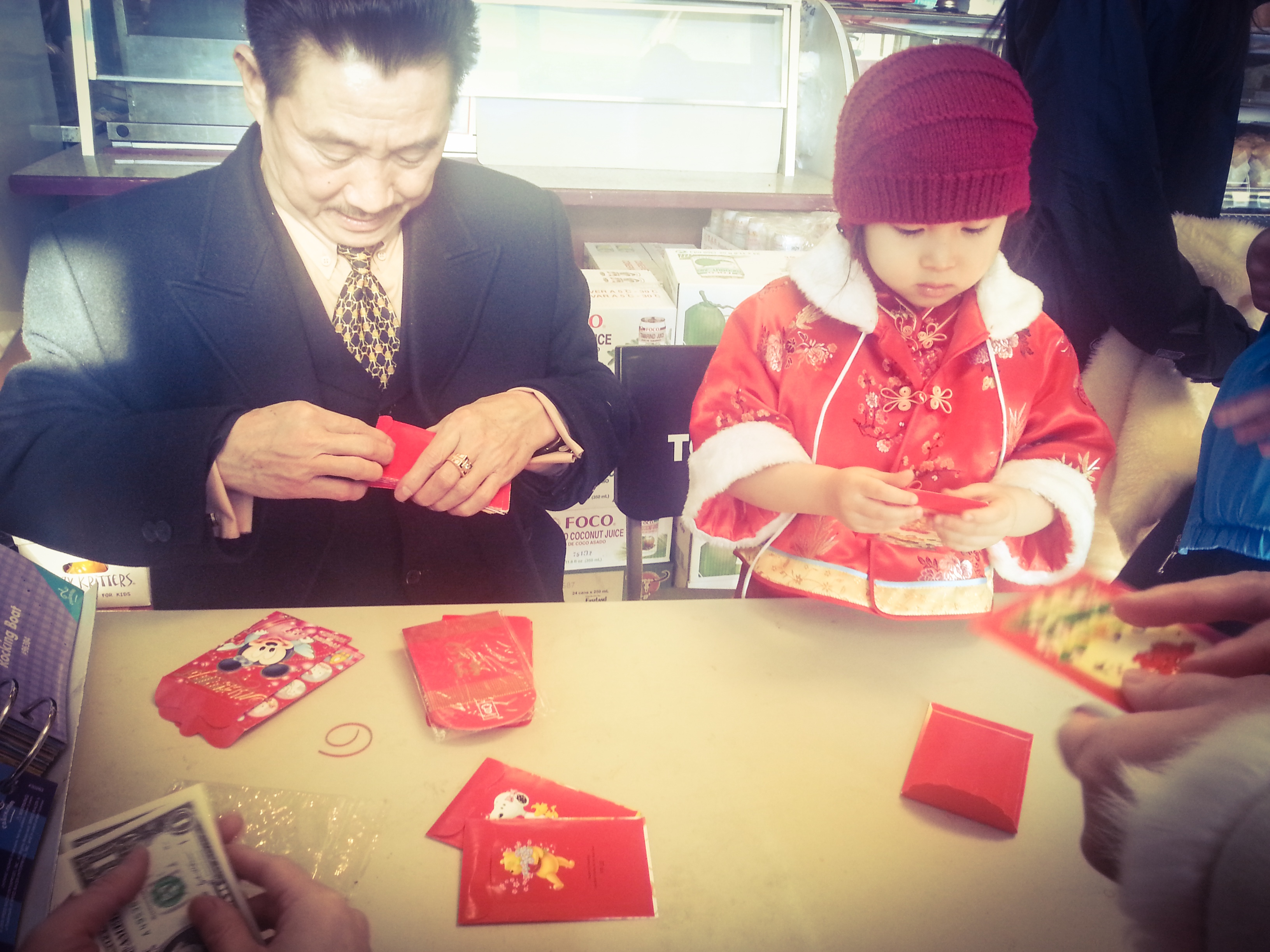 Families come together to prepare the red envelopes to hand out during Lunar New Year.